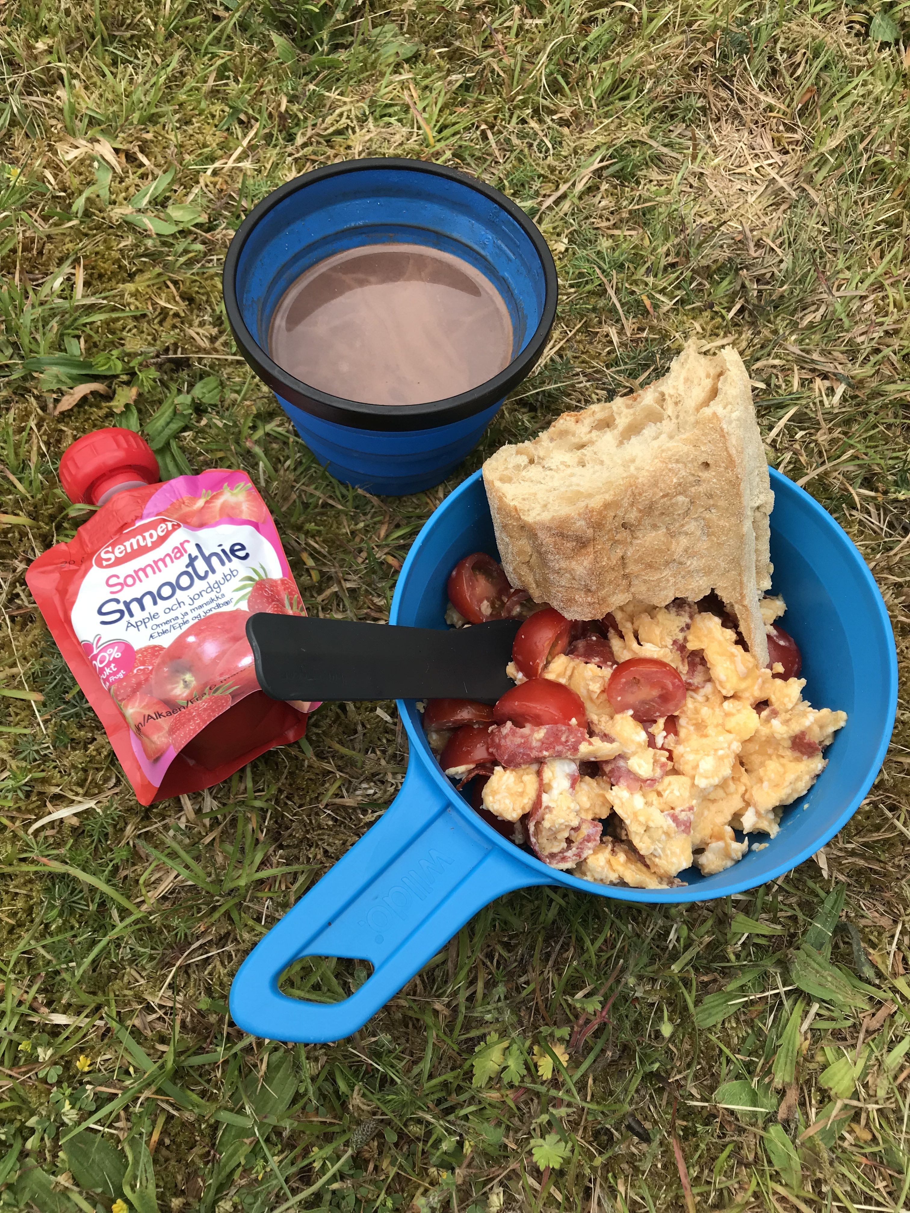 Morgenmad bestående af scrambled eggs, ristet chorizopølse, tomat, brød og baby smoothies.